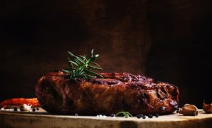 Baked pork shoulder with pepper, rosemary and garlic