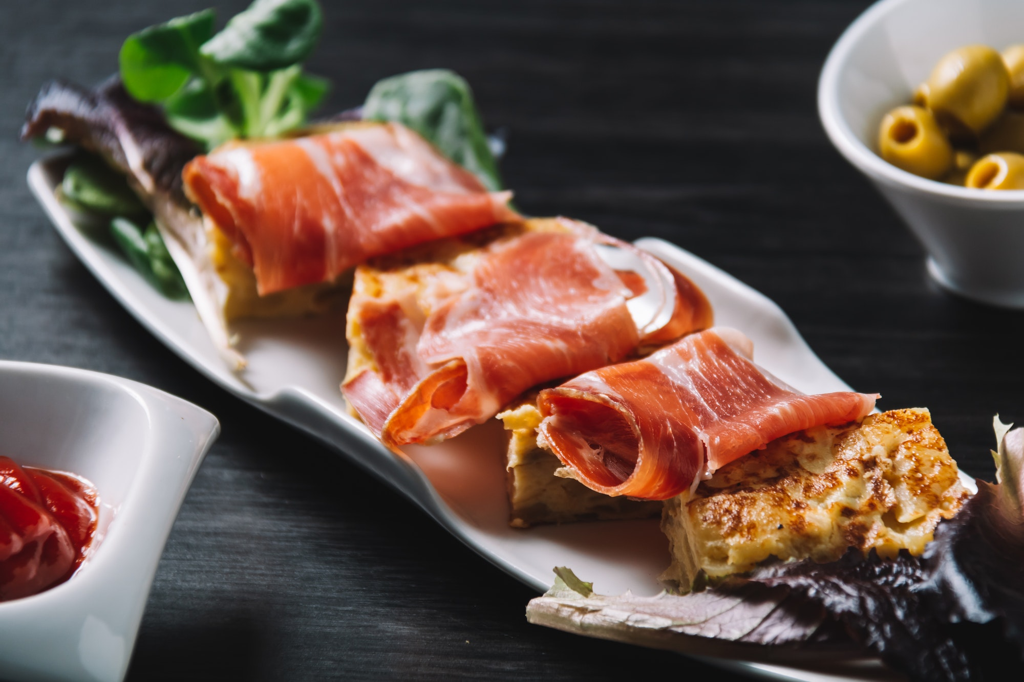 delicious Spanish potato omelette top with serrano ham, and olives