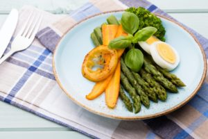 Fried asparagus with broccoli and lemon and carrot.