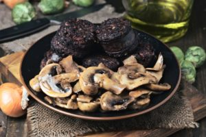 sliced mushrooms and blood sausage, fried in a porcelain dish on wood