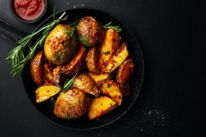 Tasty baked potato with spices and rosemary